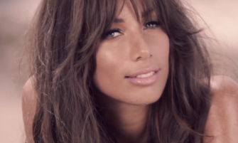 Leona Lewis looking into the camera. She has dark brown hair and blue eyes.